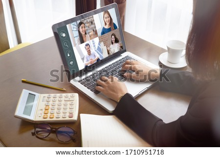 businesswoman talking colleagues about plan life in video conference. Multiethnic business team laptop online meeting in video call.smart working from home, quarantine from coronavirus covid-19