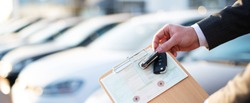 Buying a car, seller holds registration papers and keys in front of a row of new cars