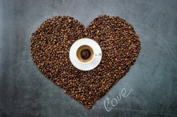 Cafes and restaurants. A mug of invigorating, black coffee and coffee beans in the shape of a heart on a dark gray background. Copy space for text. The concept of hot drinks and love.