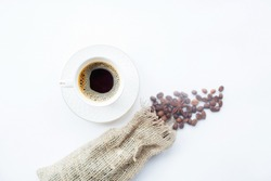 Cafes and restaurants. A mug of invigorating, black coffee and natural coffee beans in a bag on a white background, top view. Place for an inscription. The concept of food and hot drinks.