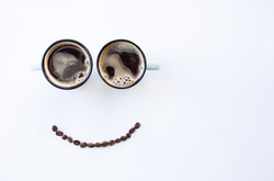 Cafes and restaurants. Two cups of coffee and a smile from coffee beans. Place for an inscription. The concept of hot drinks and good morning.