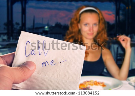 """Call me..."" message on napkin in hand against pretty girl"