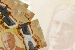 100 Canadian dollars bills lies in stack on background of big semi-transparent banknote. Abstract business background