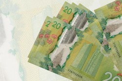 20 Canadian dollars bills lies in stack on background of big semi-transparent banknote. Abstract presentation of national currency. Business concept