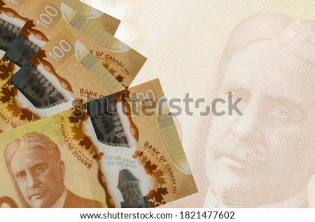 100 Canadian dollars bills lies in stack on background of big semi-transparent banknote. Abstract business background Photo stock ©