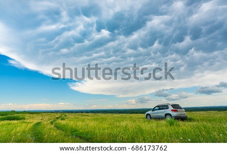 car  parked in a field on a country road #686173762