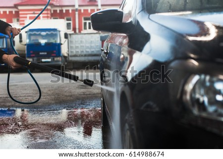 Car wash services, a man washes the car with a kercher #614988674