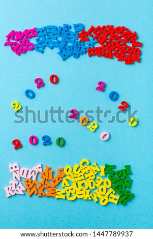 2020. card for the new year. multicolored letters on a blue background. 2020 number #1447789937