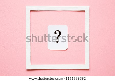 Card of question mark in white frame on pastel pink background. Soft light color. Women issues. Problem and solution concept.