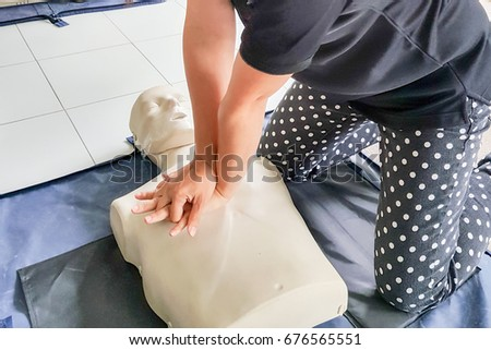 Cardiopulmonary resuscitation ( CPR )  training concept.Blur background woman student using hands doing heart pump in basic life saving and support course. #676565551