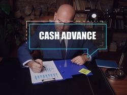CASH ADVANCE inscription on the screen. male inspecting market data. Acash advanceis a short-term loan from a bank or an alternative lender.