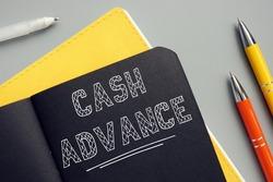 CASH ADVANCE sign on the sheet. Acash advanceis a short-term loan from a bank or an alternative lender.