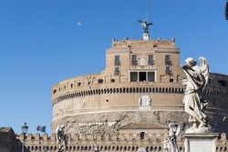 Castel Sant'Angelo (Holy Angel Castle) also known as The Mausoleum of Hadrian  and statues of angel figure on the Sant'Angelo bridge with flying bird in the background in Rome, Italy.