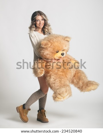 Casual smiling young woman in winter clothing holding big soft teddy bear on white background