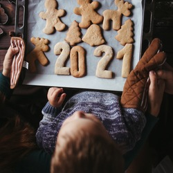 2021 celebrating New Year, Christmas magic, holiday vibes. Little boy and parents with gingerbread cookies. Family values.