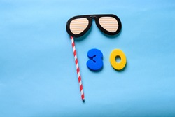 30 celebrating yellow number with sunglasses cute paper mask on straw stick . Thirty Modern alphabet digits on blue background. 30 th birthday party anniversary card.Flat lay, top view.
