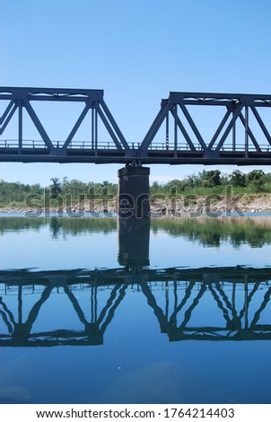 central pylon of an iron bridge over the river with reflection on the water