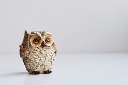 Ceramic owl figurine on a white background. Selective focus. Copy space.