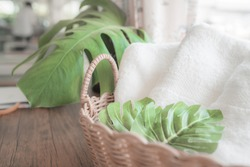 Ceramic soap, shampoo bottles and white cotton towels with green plants in basket on wood counter table inside a bright bathroom background, copy space For product display montage