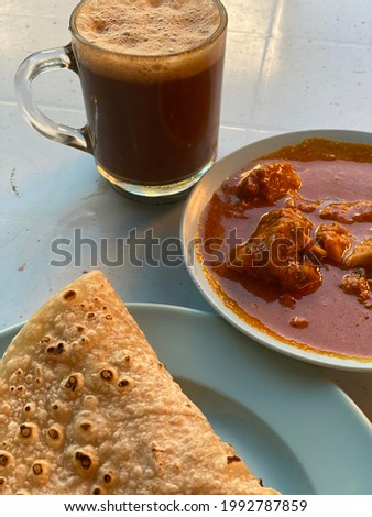 """""""Chapati', delicious breakfast meal, taken with curry and cup of steaming coffee"""