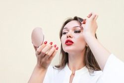 Charming  woman with big red lips in white blouse applying magnetic fake eyelashes isolated on beige color. Beauty treatment concept for cosmetologist. Pure perfect skin. Selective focus. Copy space