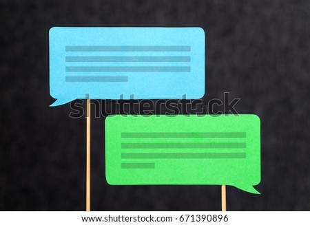 2 chat bubbles and speech balloons having discussion. Modern communication and conversation concept. Mobile and smartphone communication design made from cardboard and wooden stick. #671390896