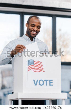 cheerful african american man voting and putting ballot in box with flag of america