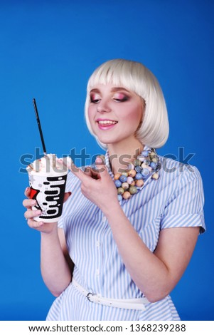 Cheerful and cheerful The girl is drinking coffee with cream. Blue background, studio. #1368239288