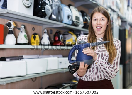 cheerful customer enjoys shopping steam cleaner in store of kitchen appliances