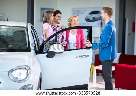 Cheerful family in car showroom in car showroom