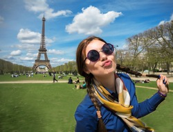 Cheerful smiling woman tourist at Eiffel Tower smiling and making travel selfie. Beautiful European girl enjoying vacation in Paris, France