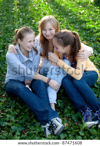 cheerful student girls sitting on the bench
