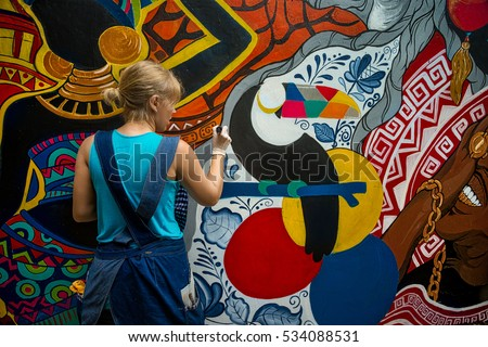 cheerful young woman painting...