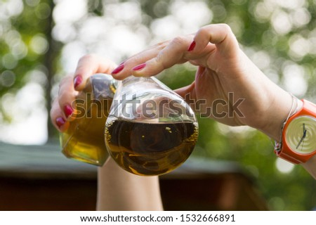 chemical experiment: pouring liquid from a bottle into a flask