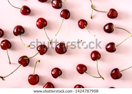 Cherry berries on a pink background top view. Background with cherry on sprigs. Cherry berries on a pink background top view. Background with a cherry on a sprig,  flat lay