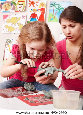 Child girl mould from clay in play room. Preschool. - stock photo