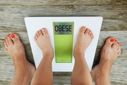 Child obesity concept with weight scale monitor and parent watching kids kilograms