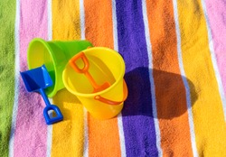 2 child's plastic sand pails and shovels on a colorful striped beach towel on a sunny day