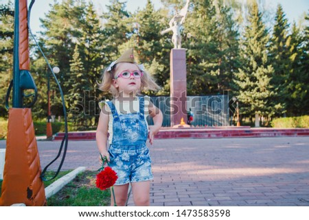 child with carnations.Near the eternal flame.