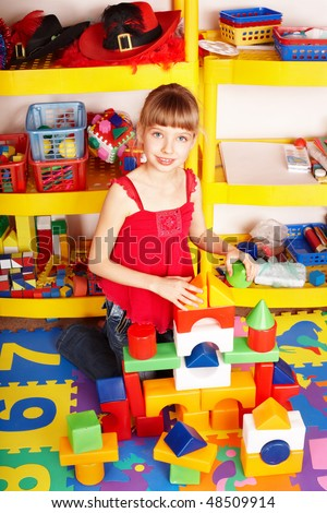 Child with puzzle, block and construction set in play room. Preschool. - stock photo