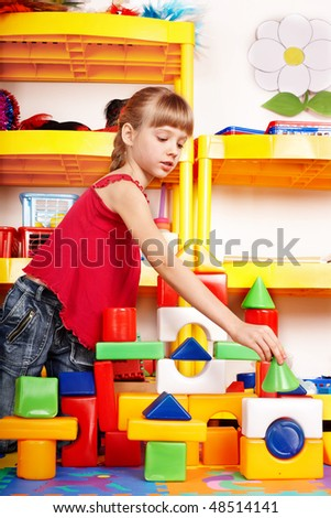 Child with puzzle, block and construction set in play room. Preschool.