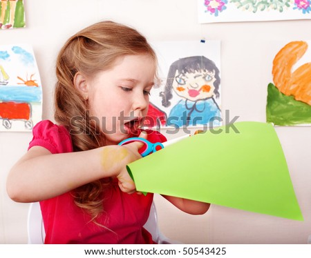 Child with scissors cut paper in play room. Preschool.