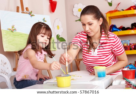 Child with teacher draw paints in play room. Preschool.