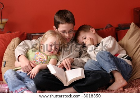 3 children at home reading a book together