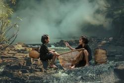 2 children fishing at the waterfall.