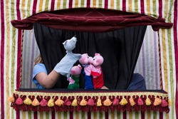 Children playing the story of the three little pigs and the big bad wolf with hand puppets in small puppet theater