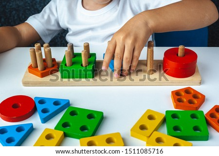 Children's wooden toy. The child collects a sorter. Educational logic toys for kid's. Children's hands close-up.  Montessori Games for Child Development