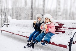 children walk in the winter forest and eat ice cream