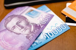 Chilean peso (CLP), money from Chile. Banknotes of 10,000 pesos and 2,000 pesos on a wooden table.