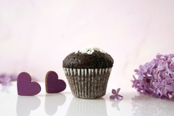 chocolate cupcake, lilac flowers and hearts on the surface with reflection